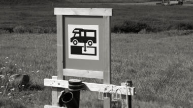 A black and white image of an RV dump station. What is an RV Black Tank?
