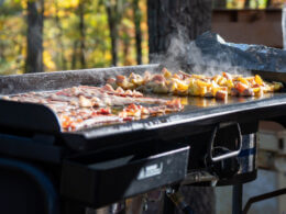 A blackstone griddle is topped with breakfast classics and makes the best meals! This one is being used at an RV campsite outside in the woods.