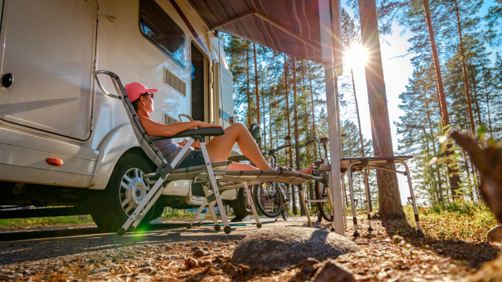 A woman stays cool by sitting under the RV awning outside with the sun poking through the forest trees.