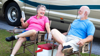 A couple sits outside their RV on a hot day and try to keep cool with cold water.