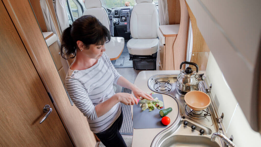 A woman cooks dinner on her own in her RV to save money and make the most of her RV budget.