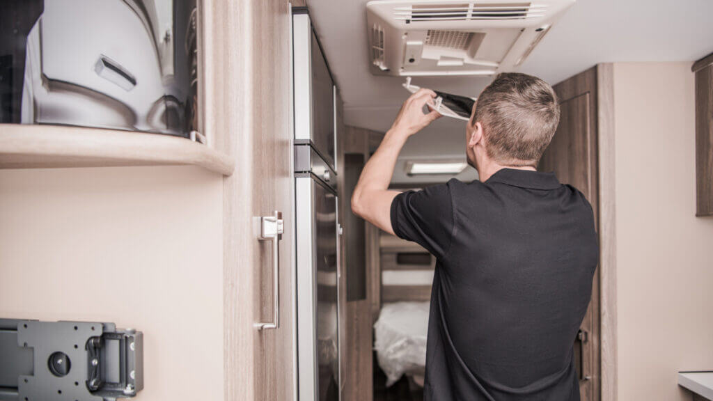 A man makes repairs on his RV to save some money and make the most of his RV budget.