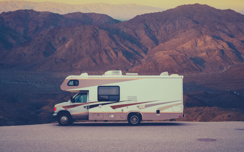 An rv parked in a open lot with hills in the background. Anyone can RV on a budget with these money saving tips!