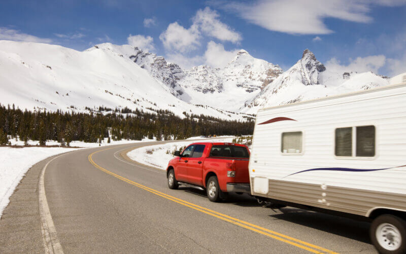 A red truck tows a travel trailer along a highway surrounded by snow and headed towards the snowy mountains! What is the best truck to tow a travel trailer?