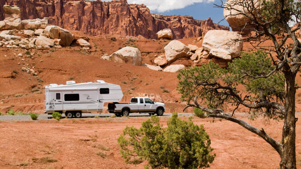 A white truck tows a white travel trailer across a highway in a red rocky area. What is the best truck for towing a travel trailer?