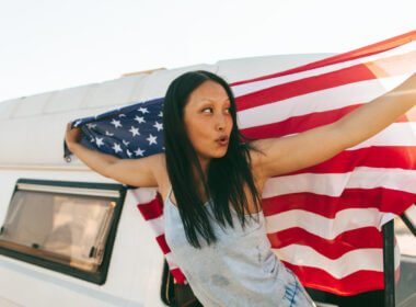 A woman holds an American flag outside the window of her RV as she sets out on her RV trip across all 50 states.