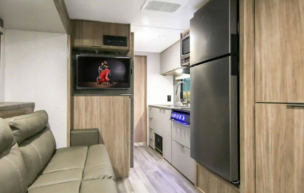 The Winnebago Micro Minnie interior with TV, couch, and fridge.
