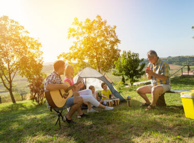 A family brought fun thing camping with and they are enjoying the trip together as the sun sets behind them.