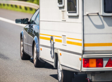 A small SUV tows a travel trailer rental with yellow stripes down the highway.