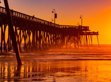 The pismo beach pier glows orange with the sunset.