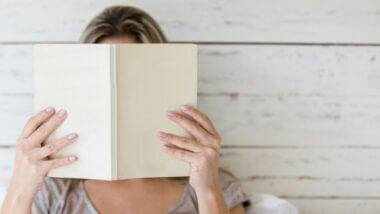 Ready to hit the road? A woman hides her face in an RV book to learn all she needs to know.