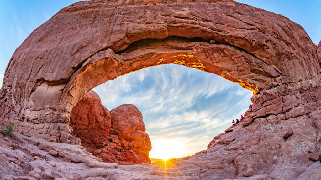 Arches national park glow in the setting sun's light with blue skies overhead.