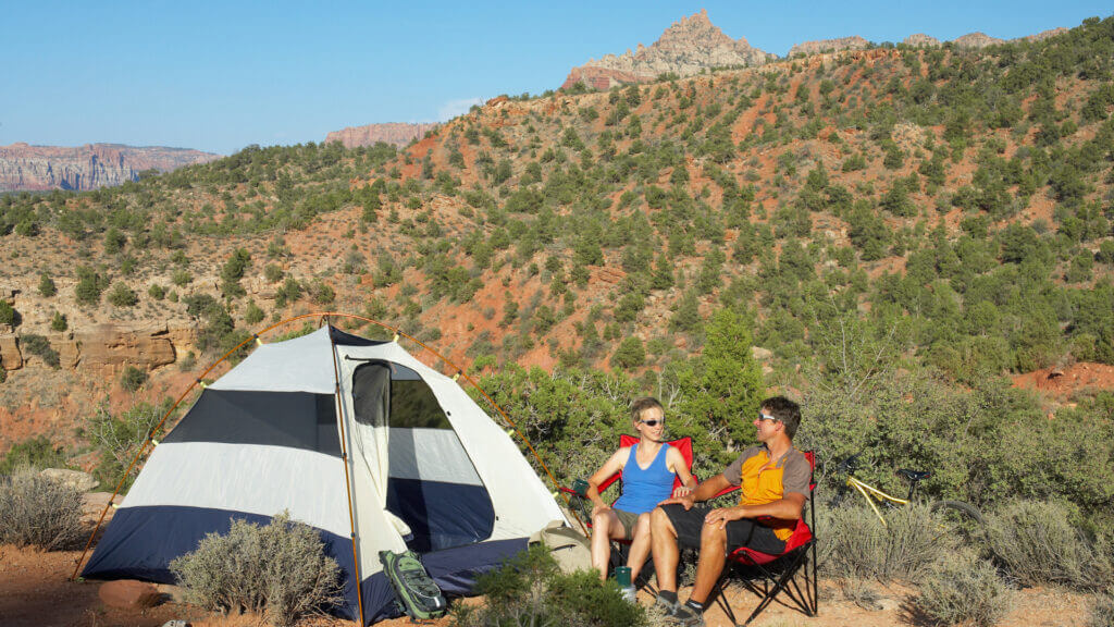 A couple sits near their tent on BLM land in Utah.