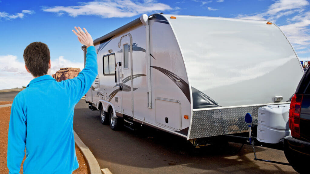 A spotter waves a  driver to stop who is reversing an RV into a driveway.
