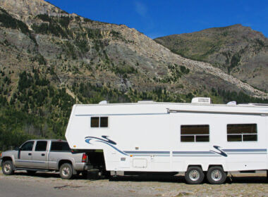 A large truck is needed to tow a fifth wheel, which is the best? This truck tows a fifth wheel alongside some brown hills.