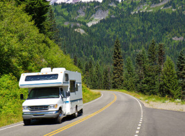 Want to know how to rent an RV for a road trip? Here is a white RV driving down a mountain road in Washington state.