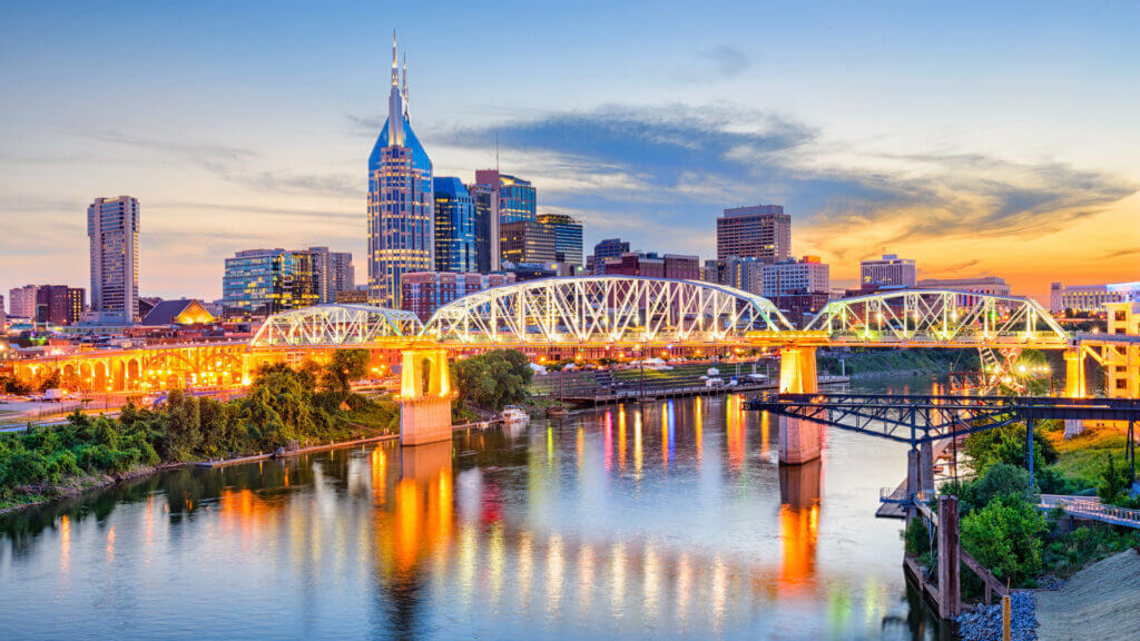 The river runs alongside downtown Nashville and the city lights reflect in the waters as the sun sets behind the skyscrapers.