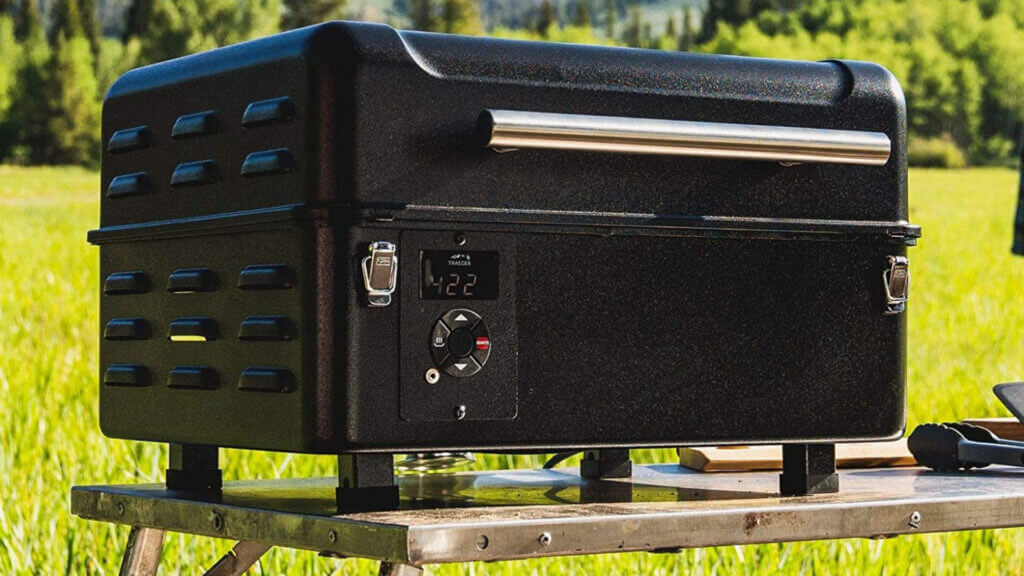 A Traeger Ranger is compact and portable sitting perfectly on a camping table in a green grass field.