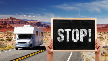 RV driving down the road with someone holding up a sign that says stop