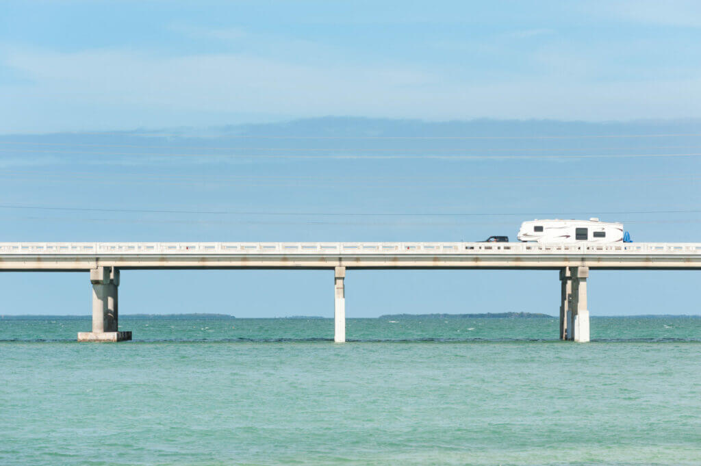 A truck and fifth wheel driving across a long bridge. When planning your RV trip to florida keys, expect a lot of bridges!