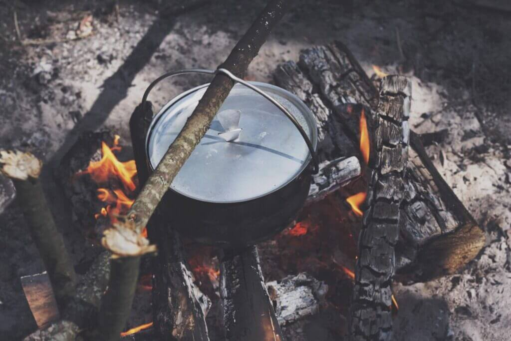 A dutch oven over an open fire with a delicious campfire breakfast inside.