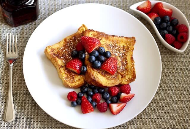 French toast on a white plate with berries on top.
