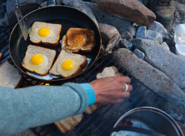 man cooking toast and eggs on a campfire