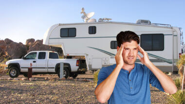A man cringes because he regrets buying a fifth wheel RV that is now parked in the desert.