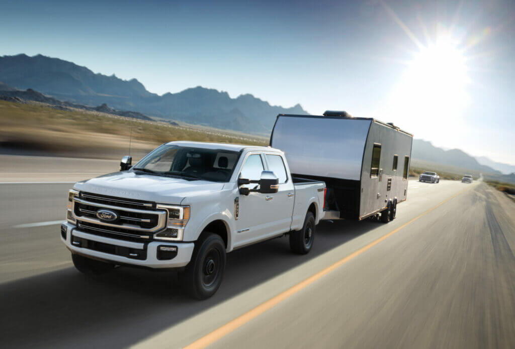 2021 F-Series Super Duty Ford Truck towing a travel trailer behind it.