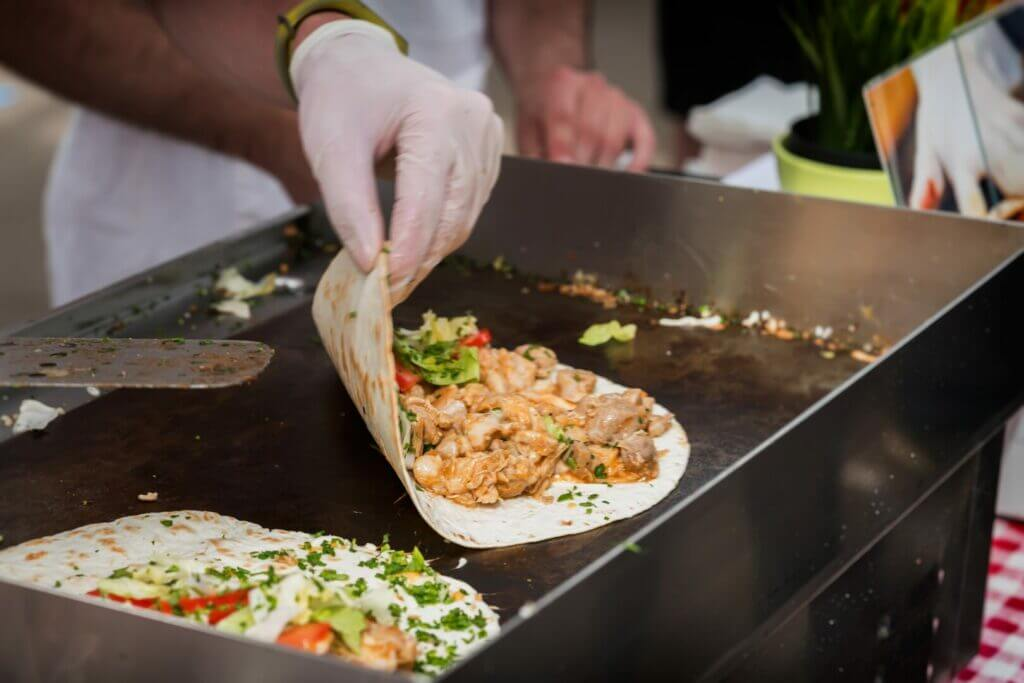 Person with gloves on cooking fajitas on a griddle. This recipe is a a great Blackstone dinner ideas.
