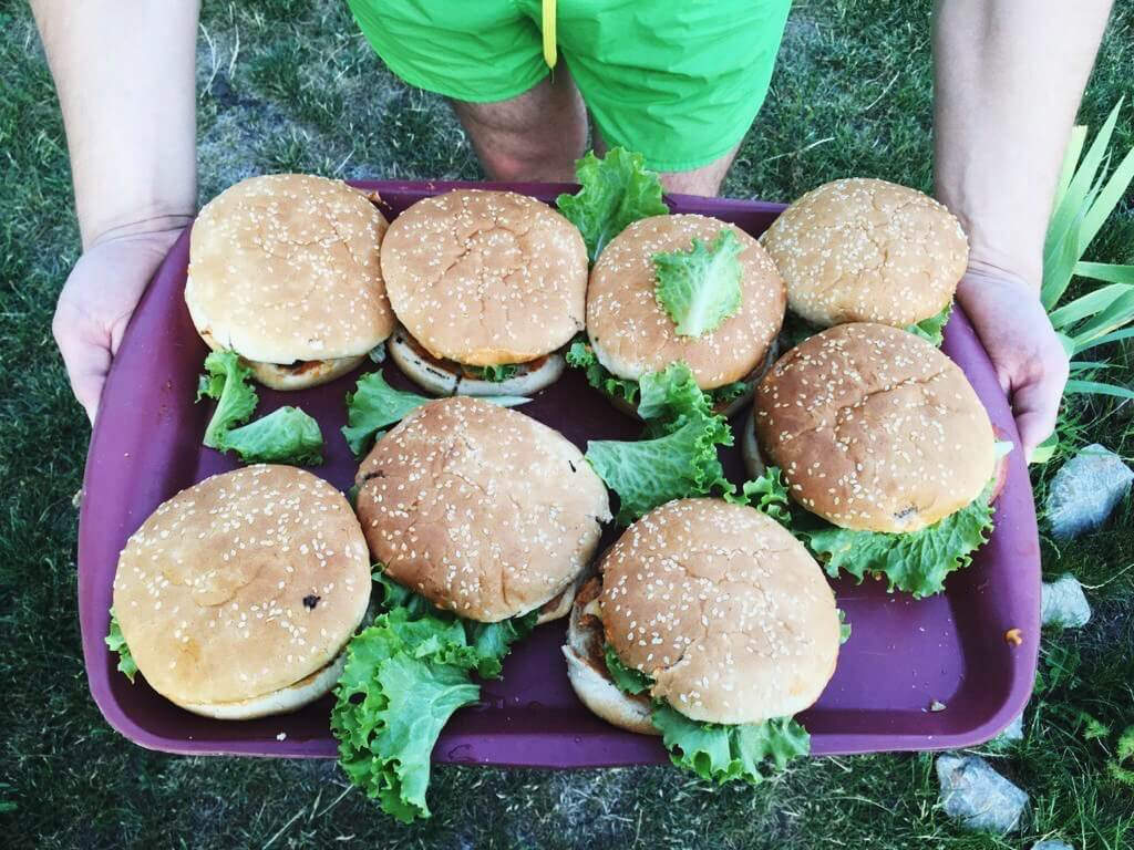 Person holding a plate of cooked burgers, a great Blackstone dinner ideas.