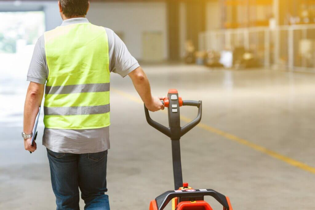 Man with a safety vest walking through a warehouse