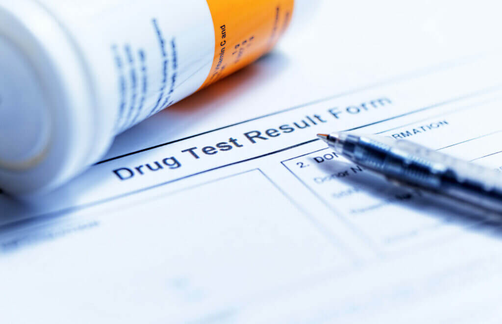 """Close up of paper that says """"drug test result form"""" with a pen and bottle of pills next to it"""