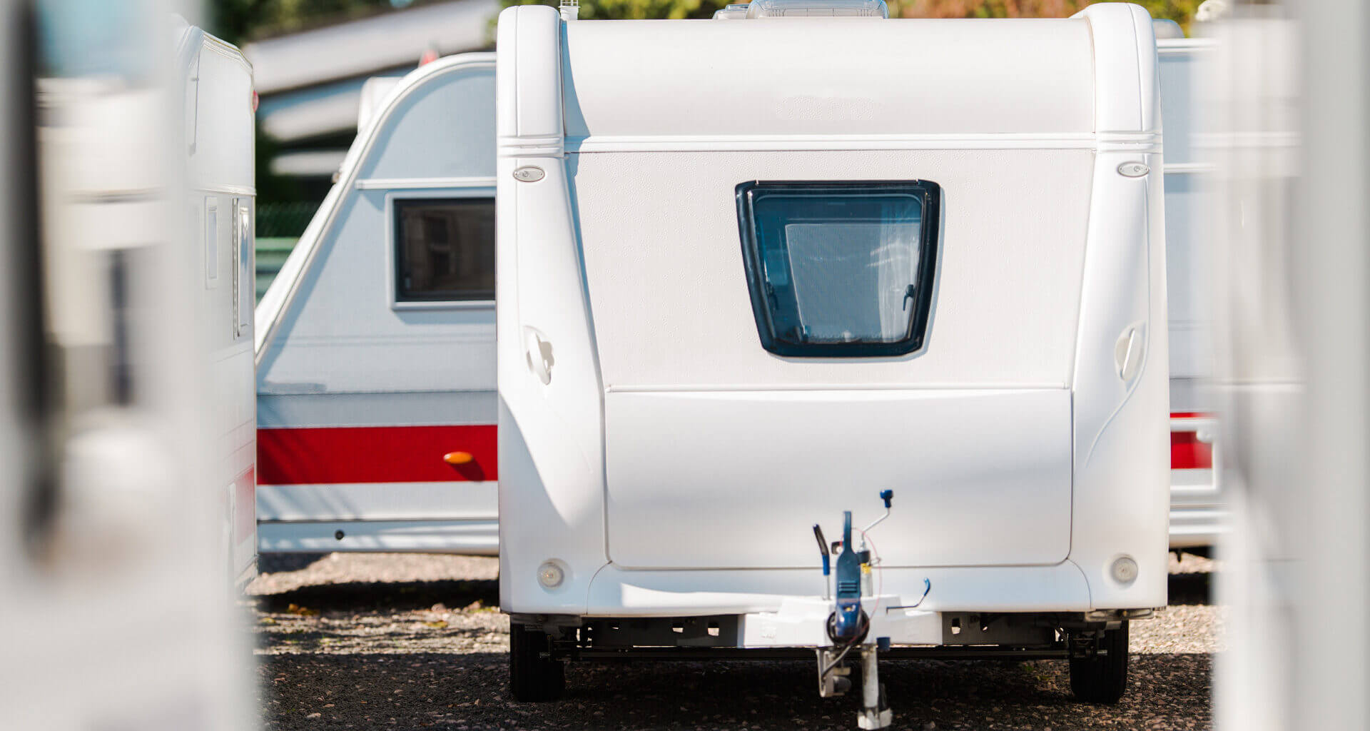 What are the best tiny travel trailers under 3500 lbs in 2021? Pictured is a tiny travel trailer parked on a sales lot around other trailers. Is it the right one for you?