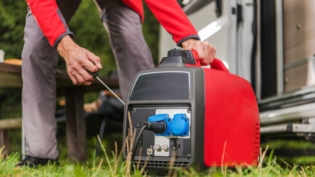 A man powers up a portable generator to power up his RV.