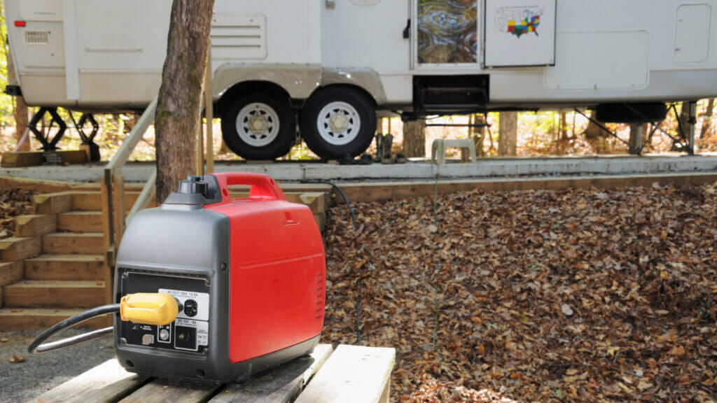A red portable generator powers an RV from a safe distance.