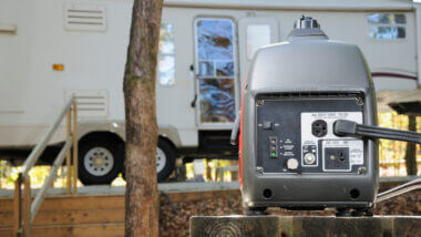 A portable generator powers an RV from a safe distance.