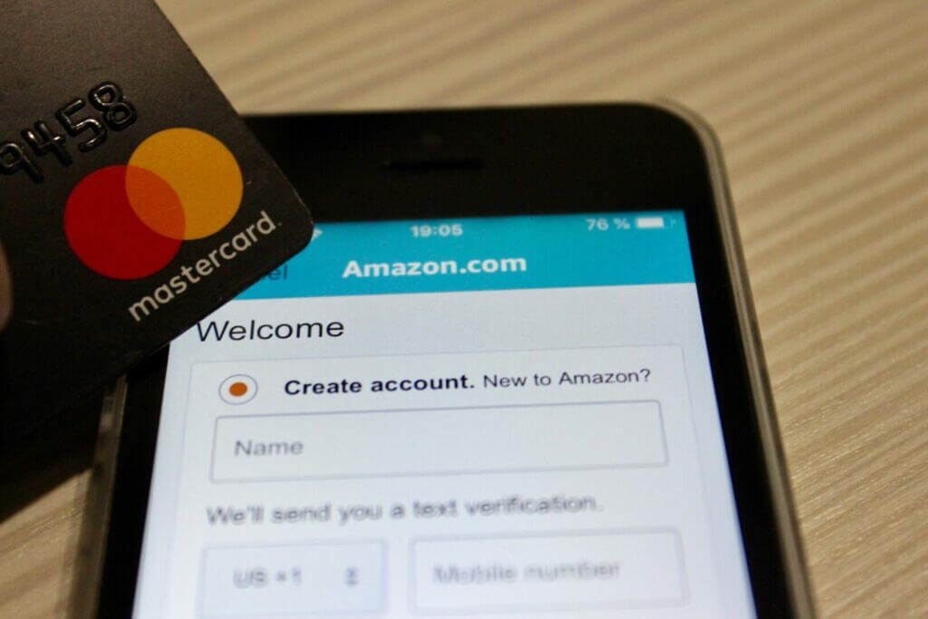 Someone holding a Mastercard and creating an account for Amazon on their phone