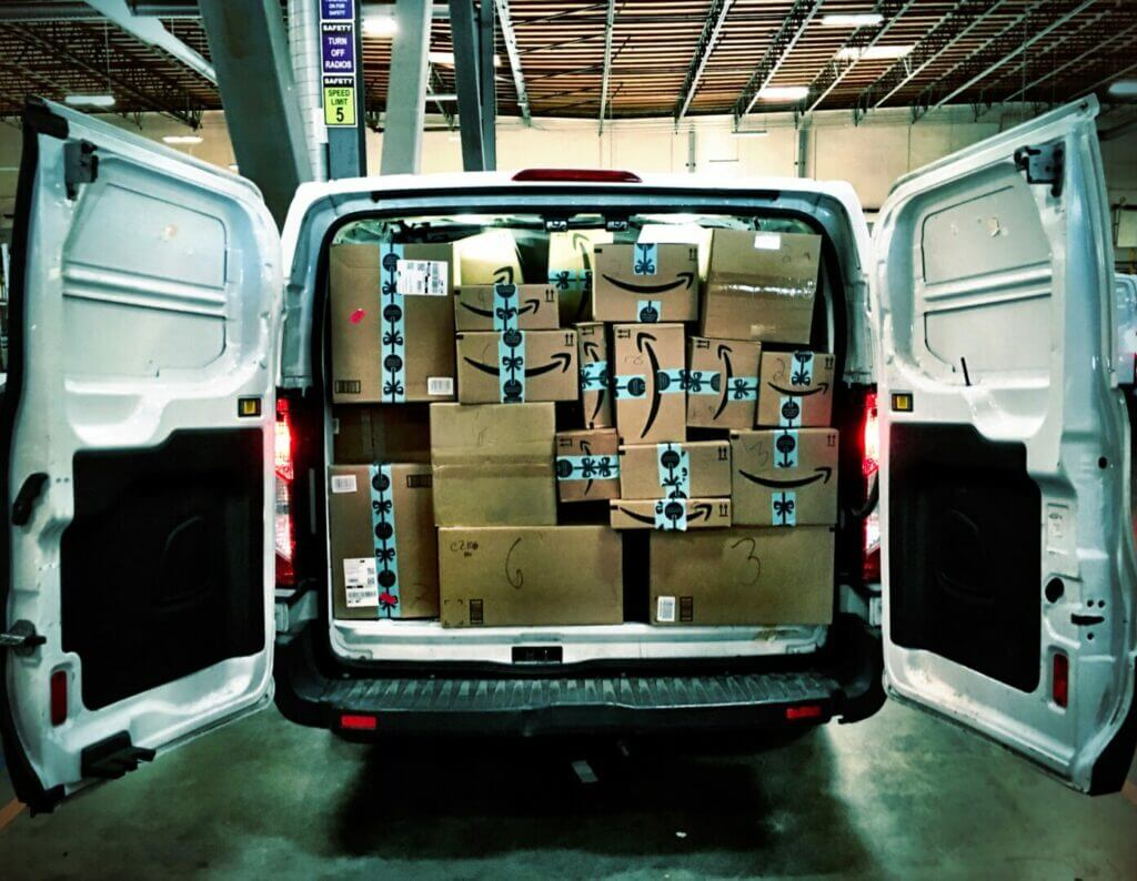 A white delivery truck with back doors open filled to the top with Amazon Prime packages
