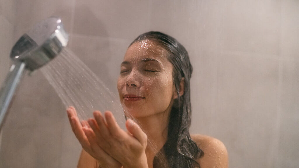 A woman enjoys strong water pressure from her shower thanks to the RV water pump.