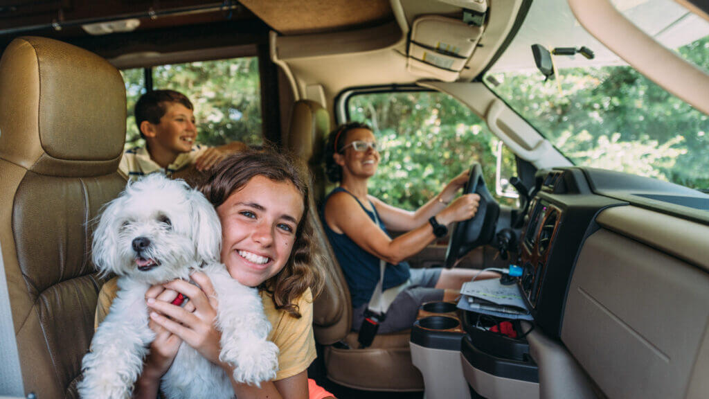 A family is smiling and happy to explore a cross country RV trip because they woke up early and hit the road before traffic.