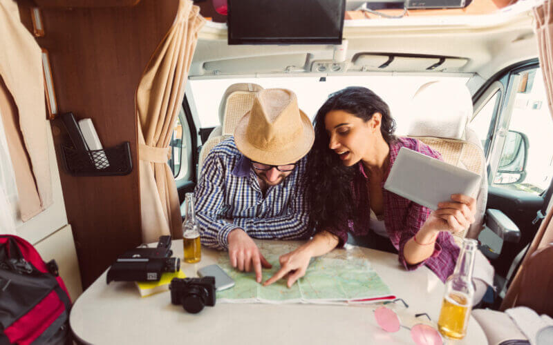 A couple fixate on a map as they drink beers and plan their first RV cross country trip.