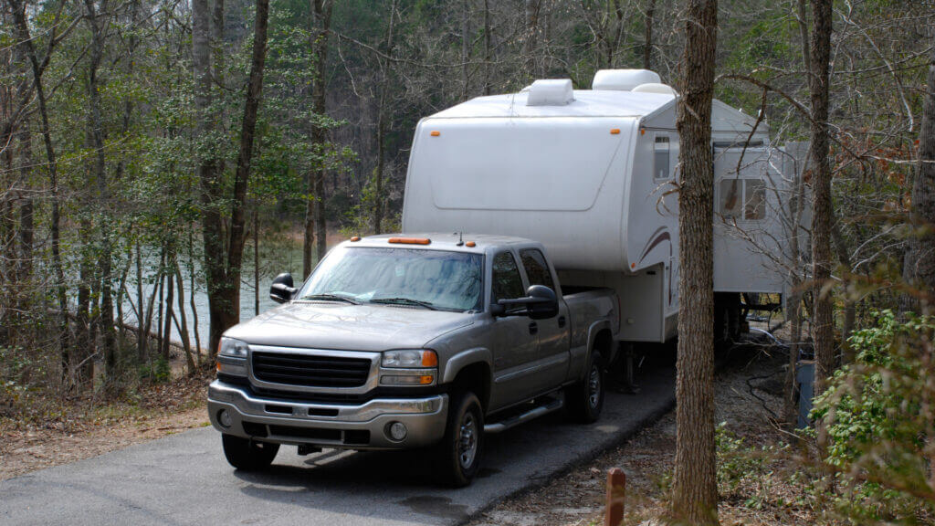 A truck reverses into a campsite with a trailer.