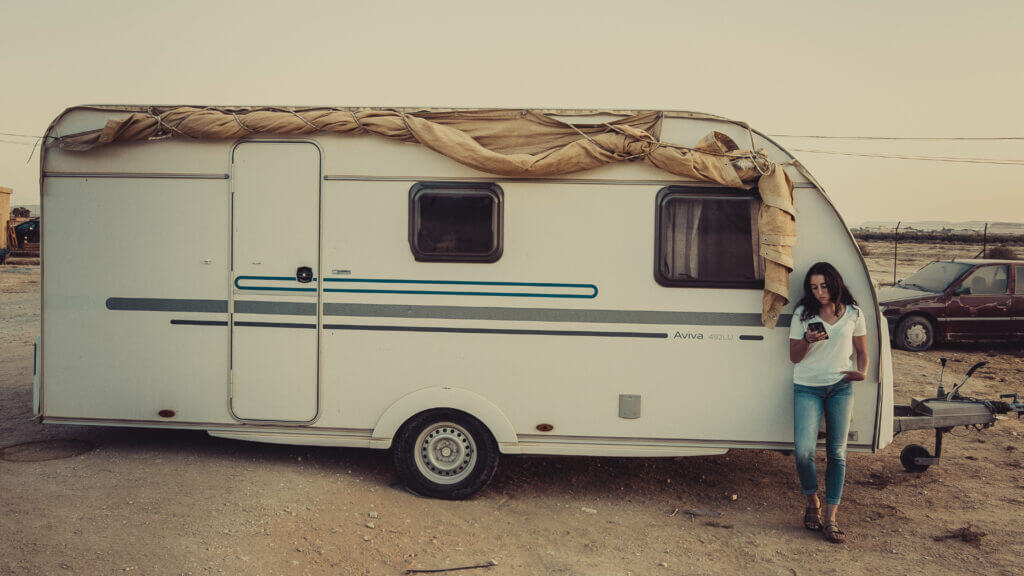 A common regret of purchasing travel trailers is the cheap construction. A girl with her cell phone stands in front of a trailer that has not aged well.