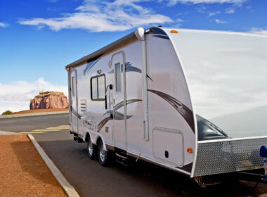 A travel trailer being pulled by a car in the desert. They may regret having a travel trailer and not an RV!