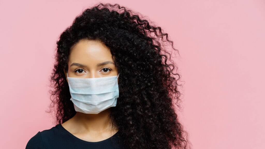 A woman wears a mask in front of a pink backdrop because if you're not vaccinated yet you still need to wear a mask to prevent the spread of Covid-19.