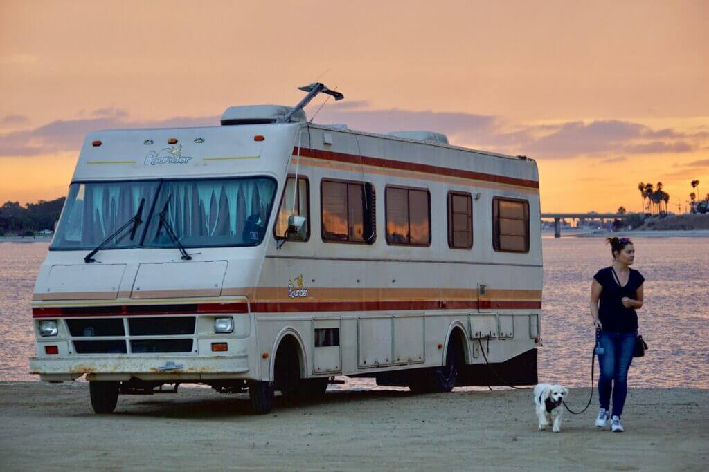 A woman walking outside her RV with dogs on a lease