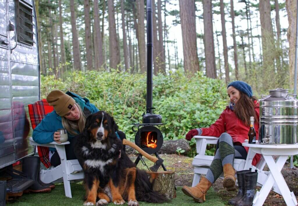 Two women sitting outside their RV with dogs and a small fire