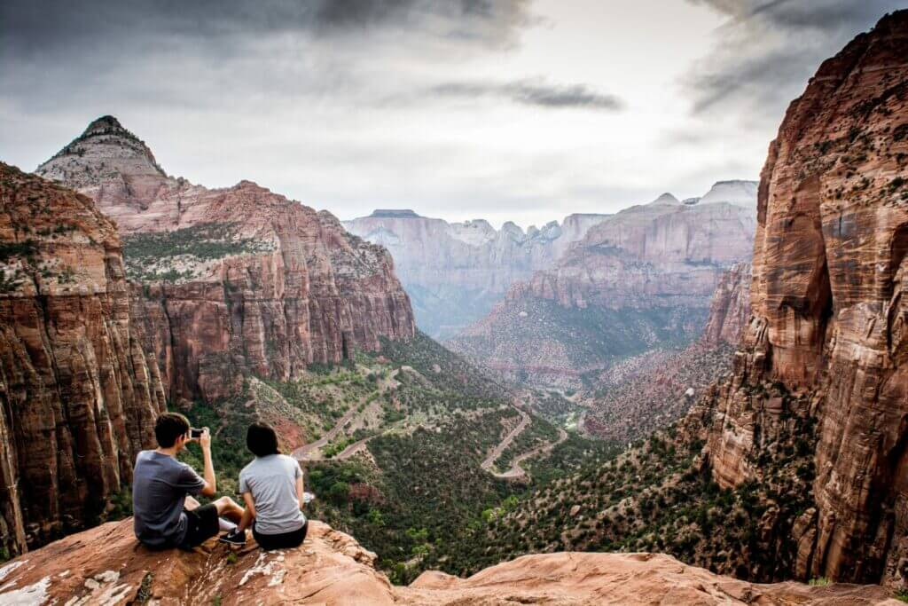 Couple sitting at the top of Angel's Landing in Zion National Park