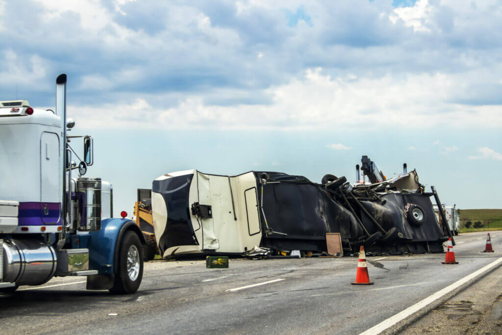Fifth wheel RV overturned on highway with wench truck trying to get it off the road and two semis parked nearby and traffic cones keeping traffic away